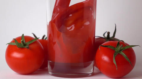 Tomatoes with leaves and tomato juice being poured into glass. Super slow motion Footage
