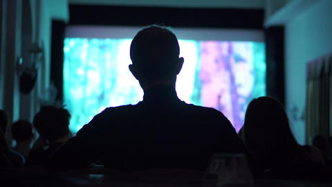 Silhouette of young man watching movie in dark cinema hall Footage