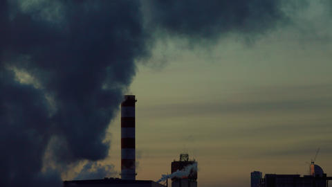 Heavily smoking factory against late evening sky. 4K video Footage