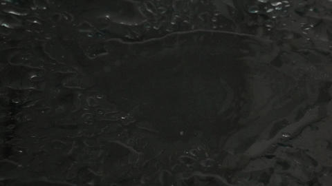 Super slow motion shot of water drops hitting wet glass surface Footage