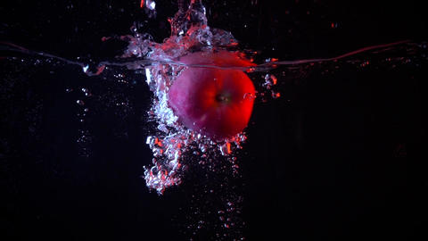 Apple falling in water super slow motion video against dark background Footage