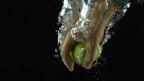 Man hand reaches and grabs green apple floating in water super slow motion shot Footage