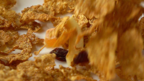 Corn flakes, dried fruits and raisin scatter on plate super slow motion video Footage