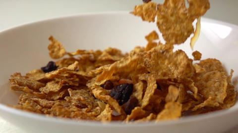 Corn flakes, dried fruits and raisin scatter on white plate super slow motion Footage