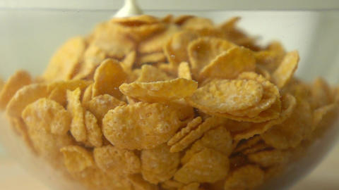 Adding some milk to corn flakes in glass bowl super slow motion shot Footage