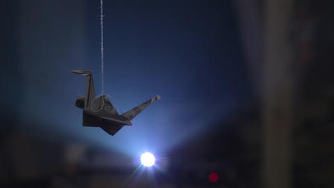 Paper origami crane hanging on thread against bright... Stock Video Footage