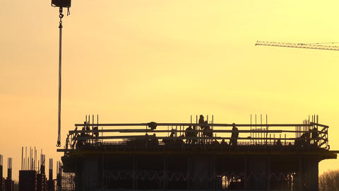 Silhouettes of construction workers against orange sky. 4K telephoto lens shot Footage