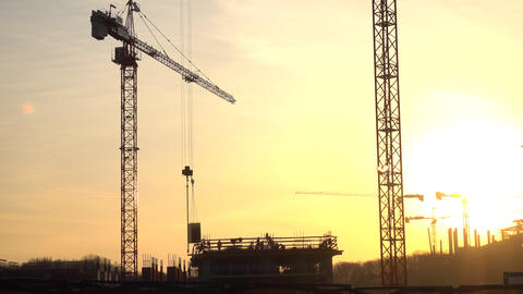 Silhouettes of crane transferring concrete plate and construction workers. 4K Footage
