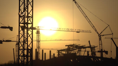 Silhouettes of cranes and construction site against orange sunset. 4K video Footage