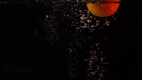Whole orange falls into water super slow motion video, orange backlight Live Action
