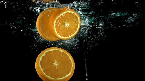 Three orange slices splash into water against black background super slow motion Footage