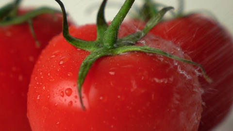 Small water drops hit red ripe tomato with green leaves super slow motion shot Footage