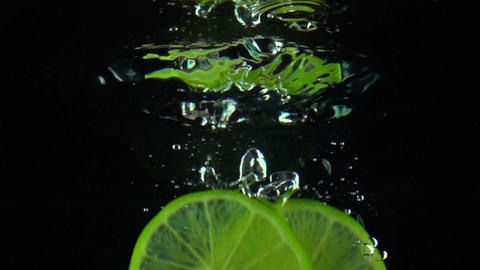Two lime slices fall under water super slow motion shot. Black background Footage