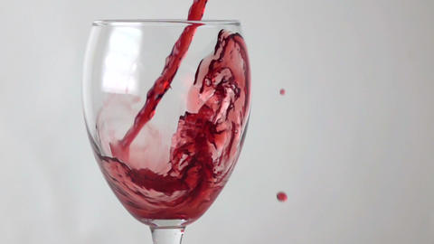 Red wine flowing into wine glass, super slow motion shot against gray background Footage