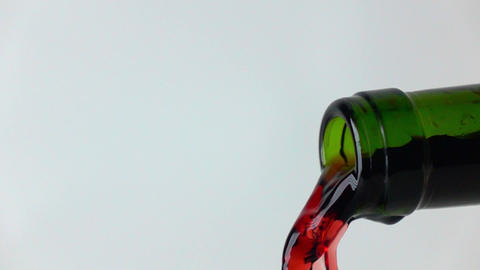 Pouring red wine from green bottle, gray background, super slow motion macro Footage