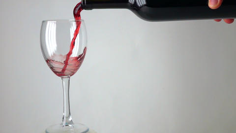 Man pouring red wine into a glass against gray background, super slow motion Footage