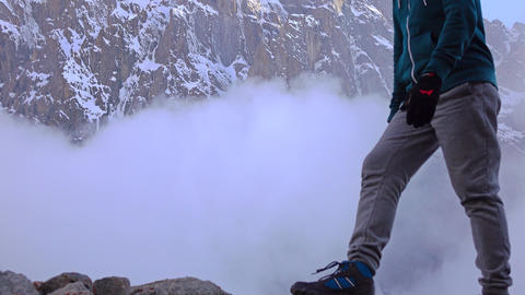 Man walks on rocks against cloudy snow covered mountains 4K video Footage