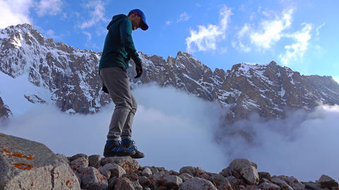 Hiker walks on rocks against cloudy snow covered mountains 4K video Footage