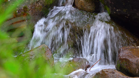 Small mountainous waterfall among lichen covered rocks. 4K close up shot Footage