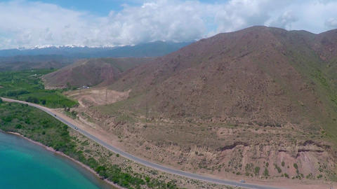 Aerial video of rural road along mountainous sea shore on sunny day Archivo
