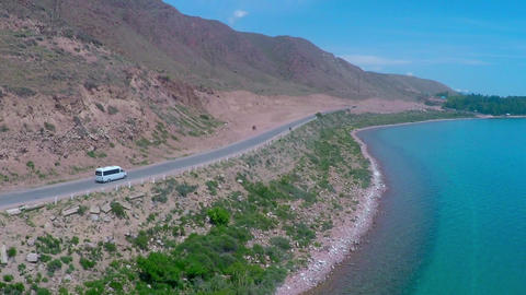 Aerial video of small white bus moving on the road along mountainous sea shore Footage