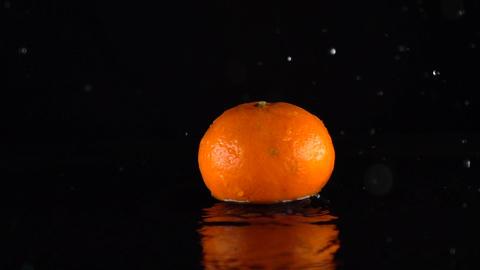 Mandarin hitting shallow water surface slow motion shot. Black background Footage