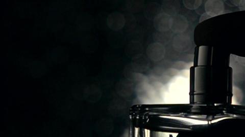 Man spraying fragrance against dark bokeh background... Stock Video Footage