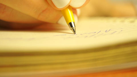 Girl with beautiful white manicure writing in her planner with a ball pen, macro Footage