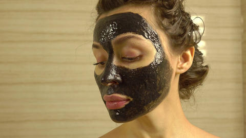 Pretty girl with cosmetic black face pack on her face. 4K video Footage