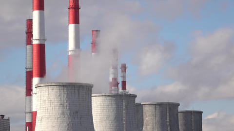 Smoke stacks and cooling towers against cloudy sky Footage