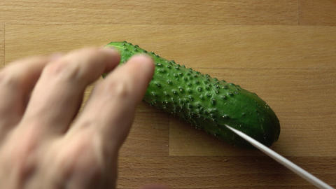 Man splitting whole green cucumber on wooden cutting board. 4K close up video Footage