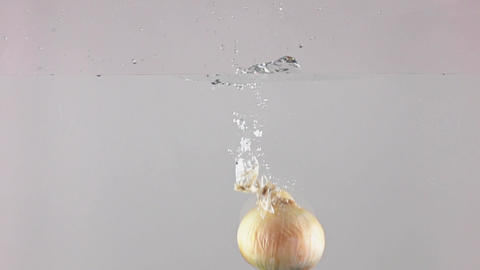 Super slow motion shot of whole onion falling into water, gray background Footage