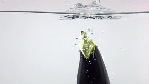 Aubergine falling down in water with splashes, super slow motion video Footage