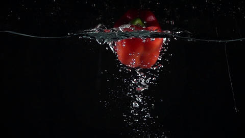 Red bell pepper falling down in water, black background super slow motion shot Footage