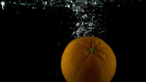 Orange falling down in water against dark background. Super slow motion shot Footage