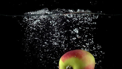 Close up shot of apple falling in water with black background. Super slow motion Footage