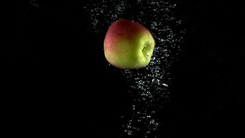 Single apple falling down in water against black background. Super slow motion Footage