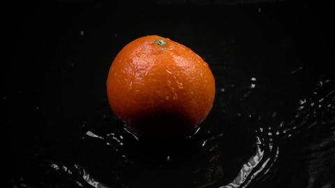 Super slow motion shot of orange hitting dark watered surface Footage