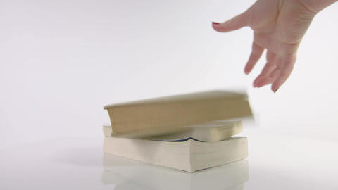 Slow motion of hand dropping a book onto a pile of books Footage