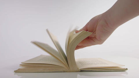 Slow motion of hand flicking through a book Live Action