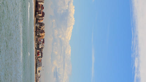 Vertical video. Clouds over the shoreline of Ostia, Rome, Italy. Timelapse Footage
