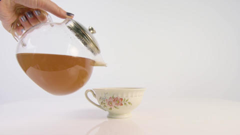 Tea being poured into a floral teacup from glass pot Footage