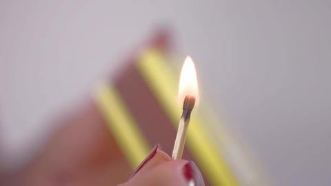 A close up of a hand holding a lit match Live Action