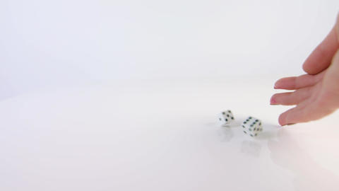 A hand throwing dice on a white background Footage