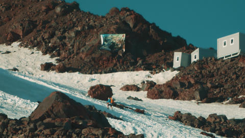 Man walks on mountain slope covered in snow using walking sticks Footage