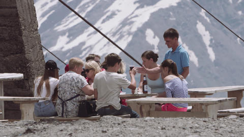 Group of family tourists dining at table on mountains trail campsite Footage