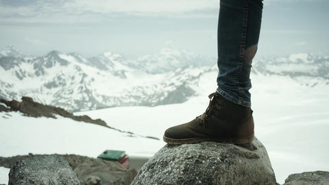 Adventurer feet in leather boot stomps on rock at snowy mountain scenic view Footage