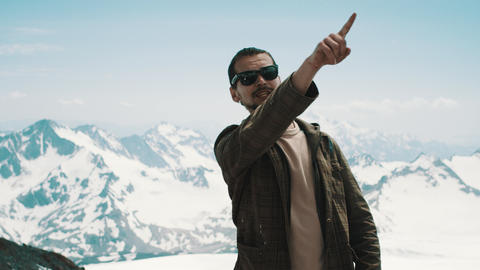 Young bearded man pointing at peaks at snowy mountains with scenic view Footage