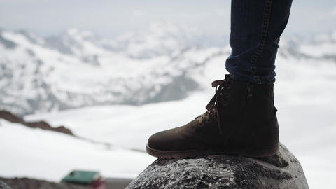 Adventurer feet in leather boot stomps on stone at snowy mountain scenic view Footage