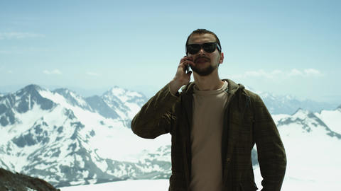 Young bearded man talking on mobile phone at snowy mountains with scenic view Footage